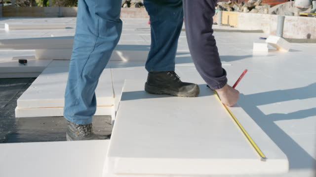 DS Male worker measuring the polystyrene foam used for insulation of the foundation