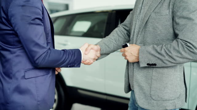 Male worker of car showroom is giving car keys to buyer young man and shking hands with him standing beside luxurious new car. Selling and buying vehicles concept. video