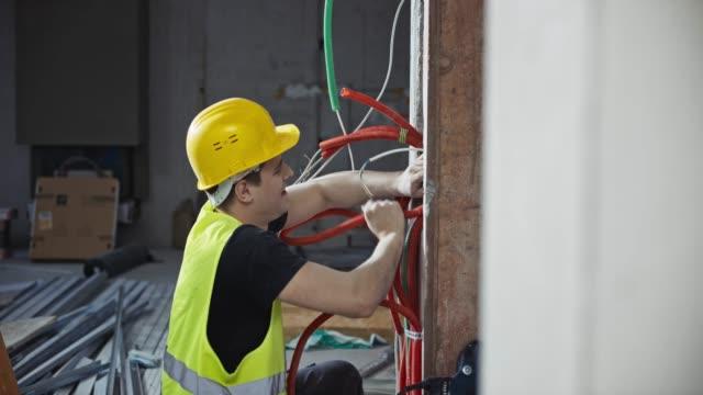 vídeos de stock, filmes e b-roll de ld trabalhador masculino colocando laranja ondulado tubos na parede - eletricista