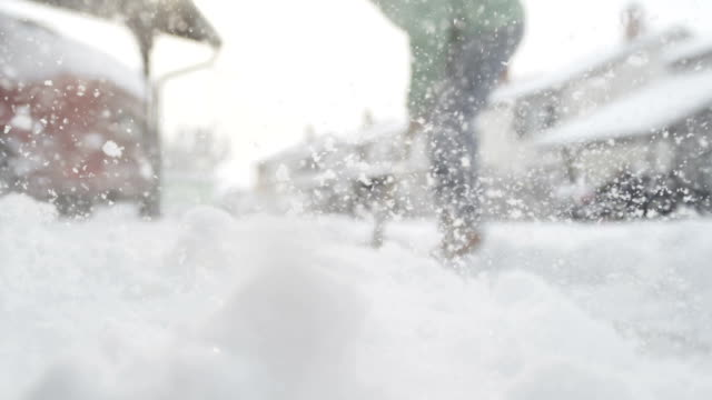 CLOSE UP: Male worker shoveling fresh snow from the front yard and making pile video