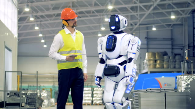 Male worker switches on a droid, then greets it in a factory facility. 4K. video