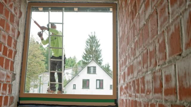 stockvideo's en b-roll-footage met mannelijke werknemer met behulp van een silicone-pistool op het glas venster terwijl staande op de ladder buiten - ladder