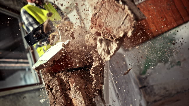slo mo male worker using a sledge hammer to break a wall - mattone video stock e b–roll