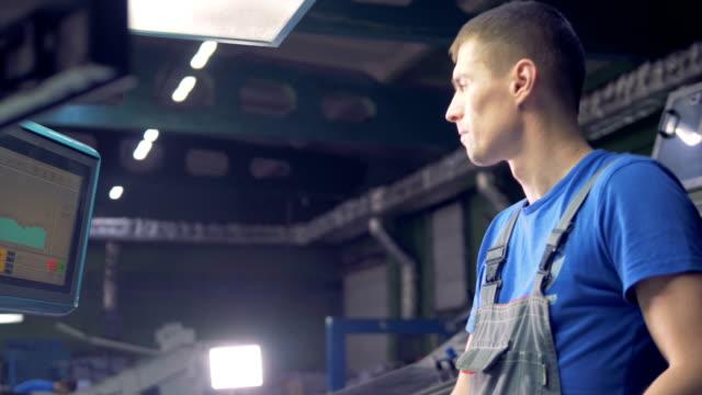 vídeos y material grabado en eventos de stock de trabajador de sexo masculino con ordenador digital con pantalla táctil en una línea de producción de la fábrica. - brigada