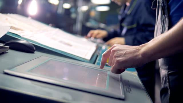 男性労働者は工場の生産ラインの横にあるデジタル コンピューターのタッチ スクリーンを使用して。 - センサー点の映像素材/bロール