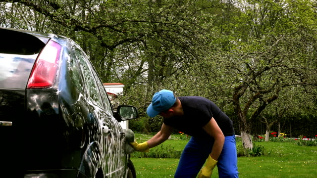 Male worker washing car on open air video