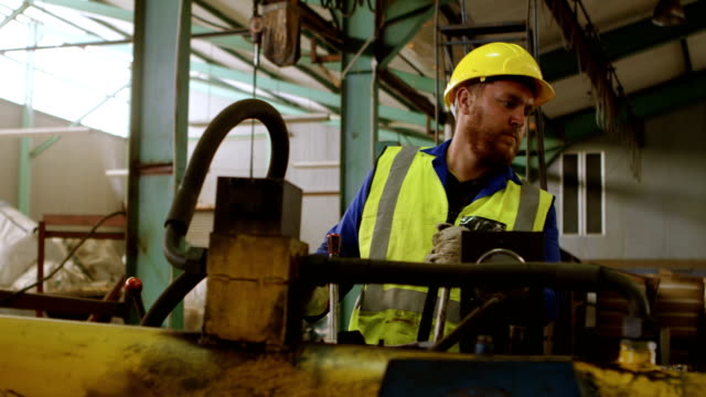 male worker working on machine in warehouse 4k - azionare video stock e b–roll
