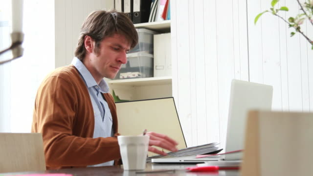 Male working from home looking at folder video