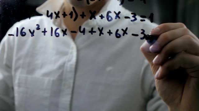 male wrote mathematical formulas on a blackboard video
