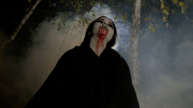 Malefic female zombie vampire getting out from a foggy forest at night in the moonlight to celebrate halloween video