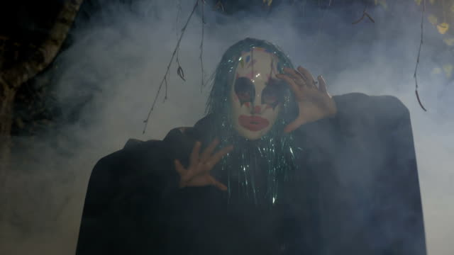 Malefic halloween funny clown wearing a mask and green fake hair performing an evil dance in a dark forest video