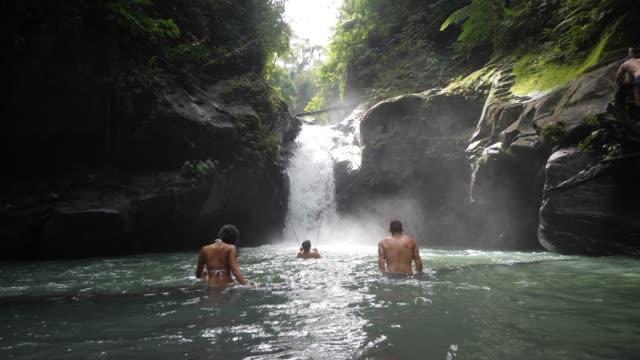 vidéos et rushes de mâles et touristes femelles se baignant dans les chutes d'eau et profitant de l'eau douce. - prendre un bain