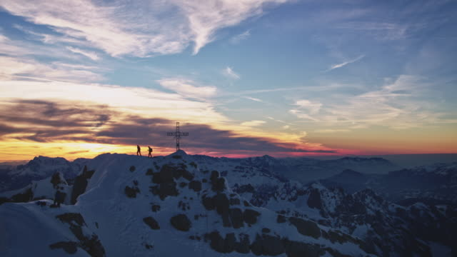 Males at mountaintop against sky during sunrise
