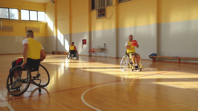 Males in wheelchair playing basketball on the court