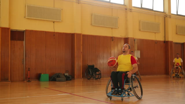 Males in wheelchair playing basketball