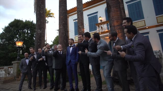 males wedding guests taking a picture with groom - young couple wedding friends video stock e b–roll