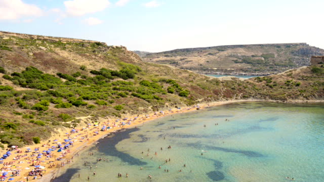 Malta Golden Bay The most popular beach in Malta, view from high up on the longest  beach with golden sand full of tourists sunbathing under blue parasols and enjoying swimming in the sea. There are three beaches separated with rock formations. malta stock videos & royalty-free footage