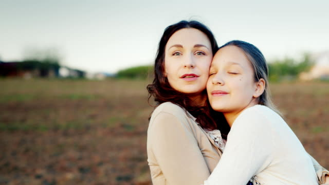 Mama gently hugs her daughter for 11 years. Together they look in one direction to the setting sun. Family values video
