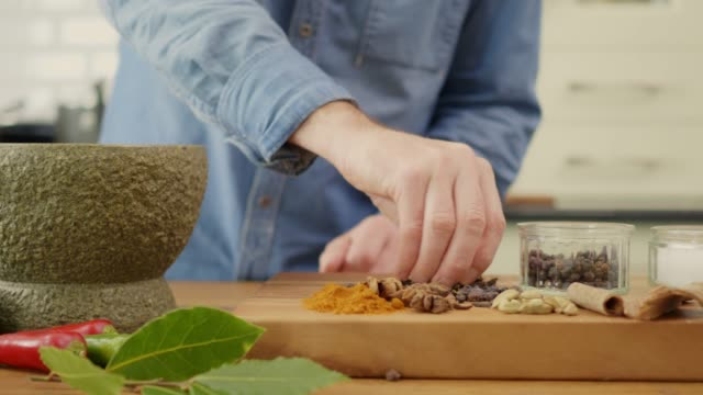 Man Adding Spices Into Stone Mortar And Grinding With Pestle video
