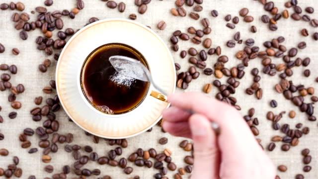 vídeos de stock e filmes b-roll de homem adiciona açúcar no copo de basquetebol e mistura-as com café. - açúcar