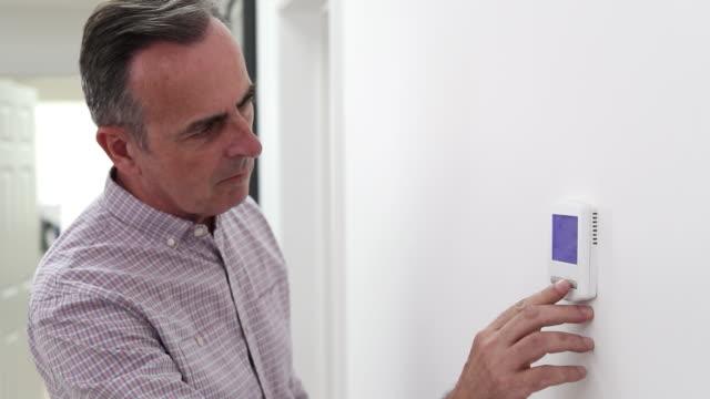 adam merkezi isıtma termostat evde ayarlama - ayarlamak stok videoları ve detay görüntü çekimi