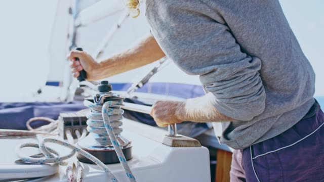 4K Man adjusting rigging and sail on sunny sailboat, real time video
