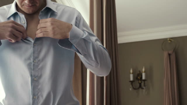 Man adjusting shirt buttons. video