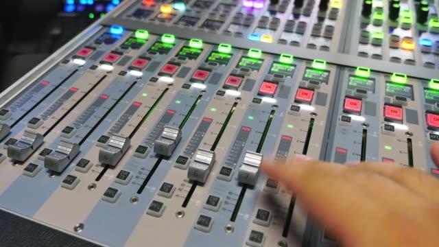 en man justera det utgående ljudet en en ljudmixer i en inspelningsstudio - intoning bildbanksvideor och videomaterial från bakom kulisserna