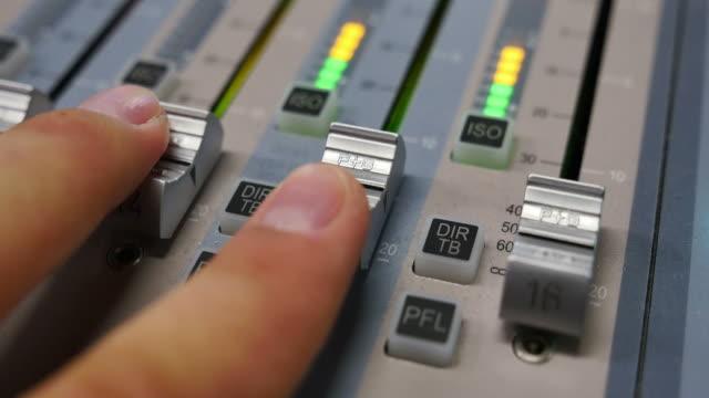 en man justera volymen på en ljudmixer - intoning bildbanksvideor och videomaterial från bakom kulisserna