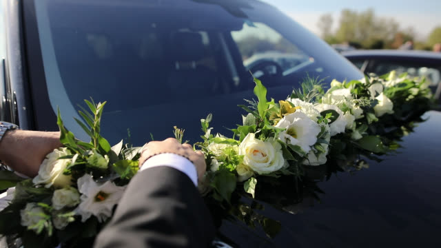 Man Adjusting Wedding Decorations on Car Hood