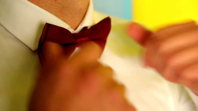 Man adjusts red bow-tie around the neck video