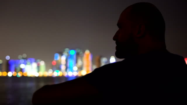 man admiring the view. cityscape in the night - точка съёмки стоковые видео и кадры b-roll