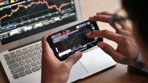 ein mann analysiert blickende börse auf dem smartphone - bitcoin stock-videos und b-roll-filmmaterial