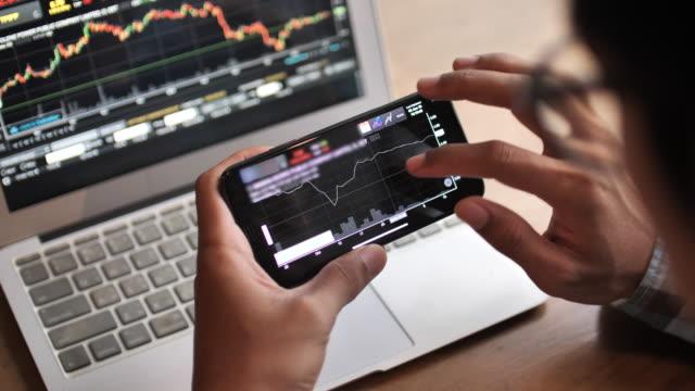 ein mann analysiert blickende börse auf dem smartphone - börsenhandel finanzberuf stock-videos und b-roll-filmmaterial