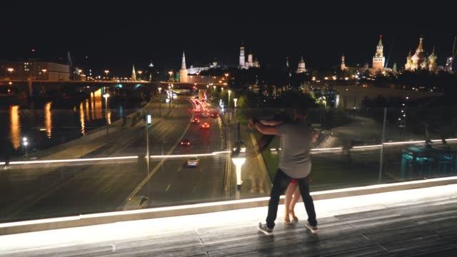 en man och en kvinna dansar på en bro i moskvas centrum. - röda torget bildbanksvideor och videomaterial från bakom kulisserna
