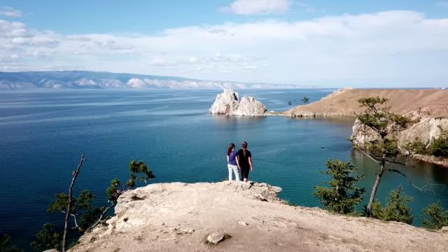 vídeos de stock e filmes b-roll de a man and a woman are standing on a cliff above the sea. lake baikal. aerial shooting from the drone. - lago baikal