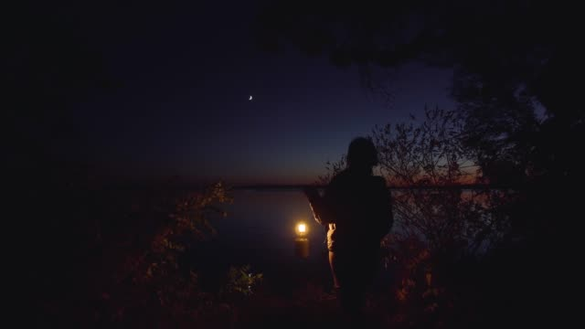 A man and a woman by the river A man and a woman are standing on the bank of a river on a dark night. They embrace and happy. flashlight stock videos & royalty-free footage