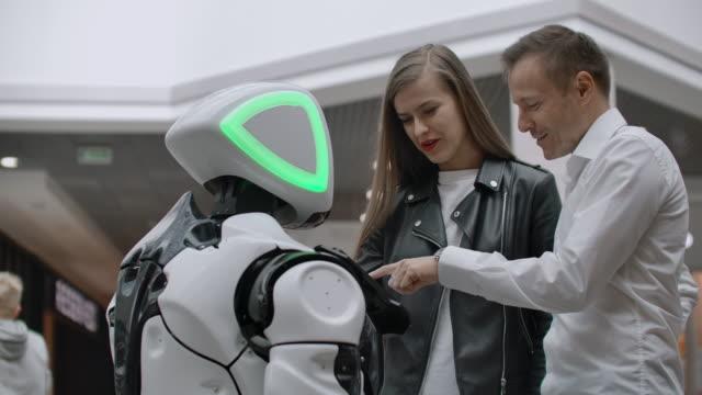 モールの男女が画面をタップして笑顔でロボットコンサルタントと交流。サイボーグアンドロイドは、人々を助けます。 - 展示点の映像素材/bロール