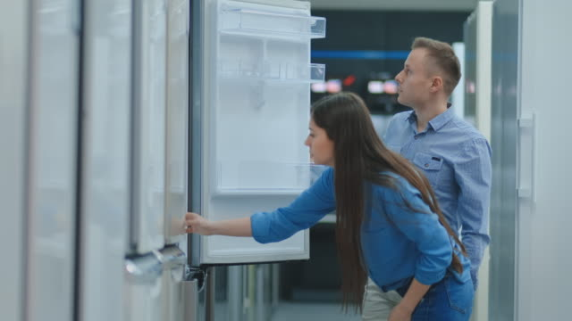A man and a woman open the refrigerator door inspect the design and quality before buying in the store A man and a woman open the refrigerator door inspect the design and quality before buying in the store. appliance stock videos & royalty-free footage