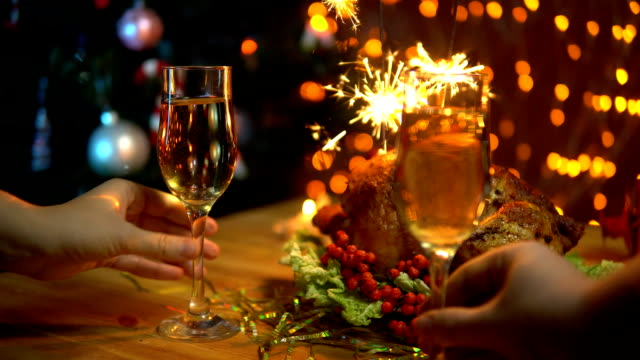 A man and a woman raise glasses of sparkling champagne over a festive table. video
