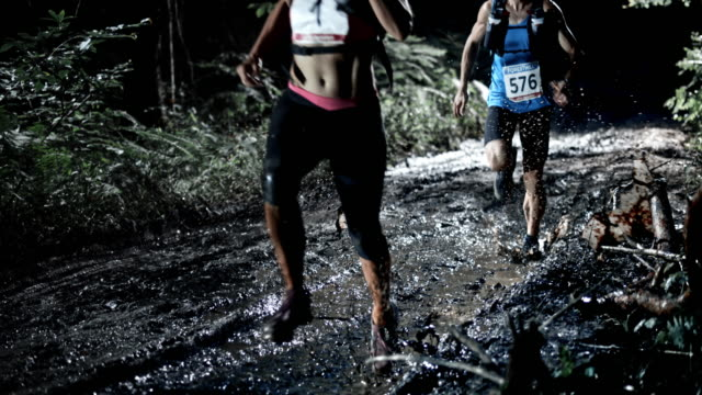 SLO MO DS Man and a woman running a night trail marathon video