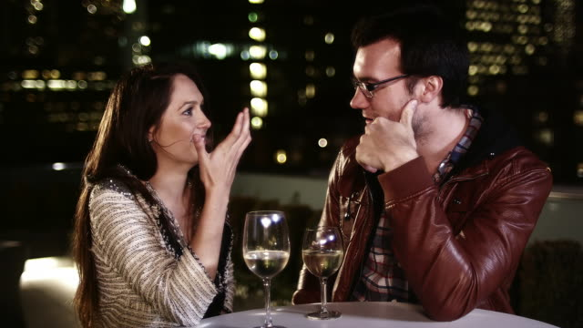 A man and a woman sit at a table with drinks and flirt and talk at night video