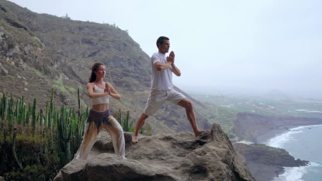 a man and a woman standing on the edge of a cliff overlooking the ocean raise their hands up and inhale the sea air during yoga. - armonia video stock e b–roll