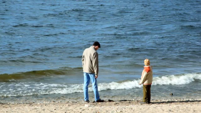 Man and boy in coast throws stones at river video