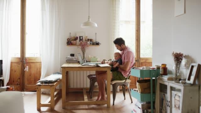 vídeos y material grabado en eventos de stock de hombre y niño jugando con el juguete en la mesa en la cocina - padre que se queda en casa