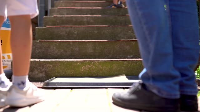 man and boy standing in disinfection door mat before walking up the steps - tappeto video stock e b–roll