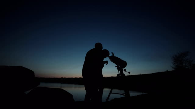 man and boy using telescope - astronomia video stock e b–roll