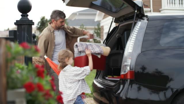 男と子供のピクニックのための車のパッキング - 荷造り点の映像素材/bロール