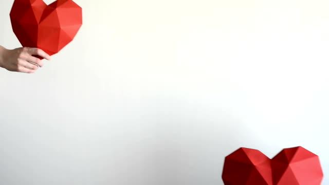 mann und weibliche hände nähert sich polygonale papier herzformen - woman and polygon stock-videos und b-roll-filmmaterial
