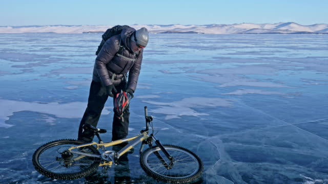 man and his bicycle on ice. the cyclist is dressed in a gray down jacket, backpack and helmet. ice of the frozen lake baikal. the tires on the bicycle are covered with special spikes. - bike tire tracks video stock e b–roll